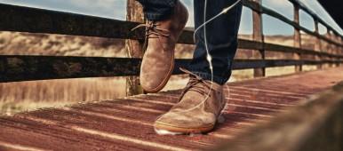 Ein Mann läuft mit Barfußschuhen aus Wildleder über eine Holzbrücke.