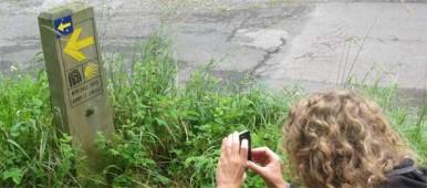 Eine schöne Frau fotografiert ein Wegweisschild auf dem Jakobsweg.