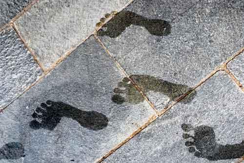 Man sieht Fußabdrücke auf einem Steinboden