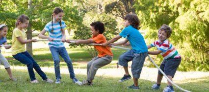 Kinder, die spielen und tauziehen machen