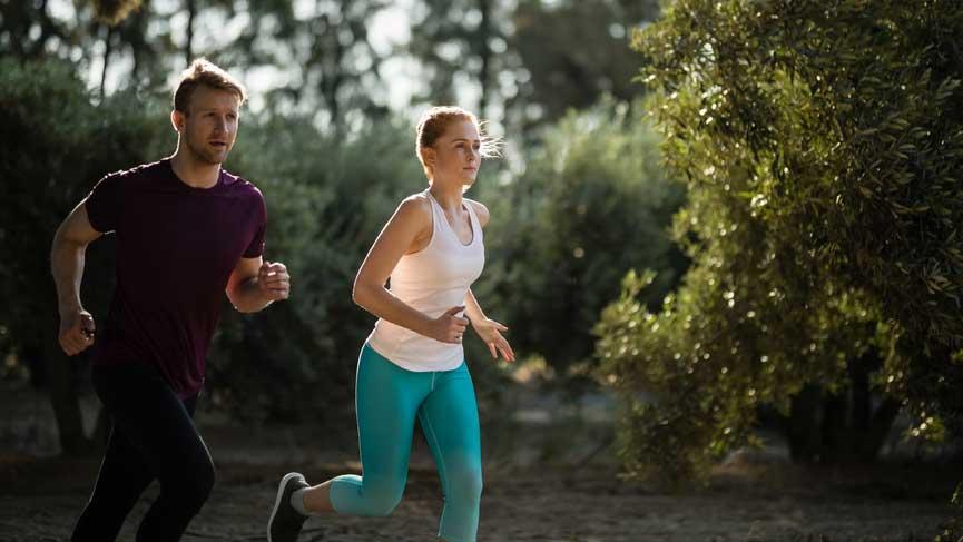 Ein Mann und eine Frau joggen durch den Wald