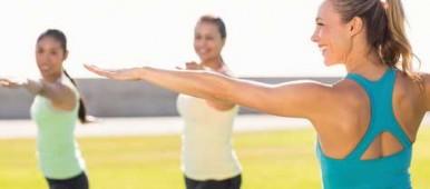 Drei Frauen stehen auf einer Wiese und üben Yoga