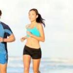 Eine Frau und ein Mann joggen am Strand entlang