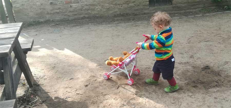 Ein Kind schiebt einen Spielzeug-Kinderwagen und hat dabei Filii-Schuhe an