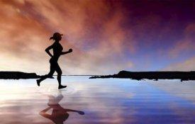 Eine Frau läuft am Strand entlang.