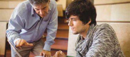 Ein Professor erklärt seinem Studenten etwas am Bildschirm in einem Vorlesungssaal
