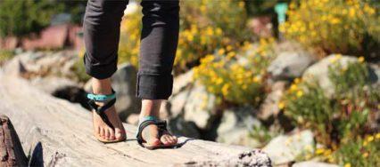 Eine Frau läuft über einen Holzsteg. Sie hat Luna Sandalen an. Zu sehen sind nur Füße und Unterschenkel.