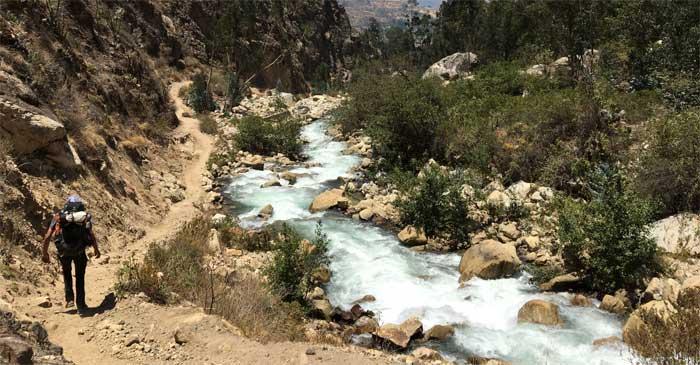 Ein Wanderer geht durch ein steinige, felsige Schlucht, die von einem Bach durchzogen wird.