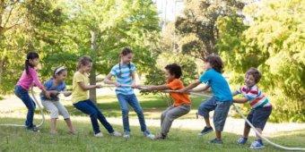 Kinder spielen bei sonnigem Wetter in einem Park Tauziehen