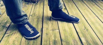 Man sieht zwei Füße mit Leguano Barfuß-Socken in blau, die auf Holzdielen stehen.
