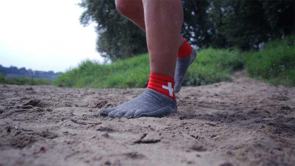 Man sieht einen Sandboden. Jemand hat die Free Your Feet Socken an und läuft damit über den Sand.