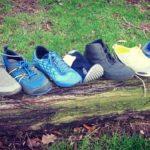 Eine Auswahl der Barfußschuhe Testsieger von Barfuss-Schuhe.Net aufgreiht auf einem Baumstamm