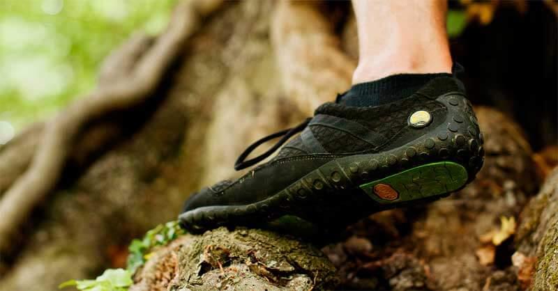 Man sieht den Fuß eines Mannes in Nahaufnahme, der über die Wurzeln eines Baums läuft. Am Fuß ein Schuh von Joe Nimble, und zwar der Nimbletoes in schwarz.