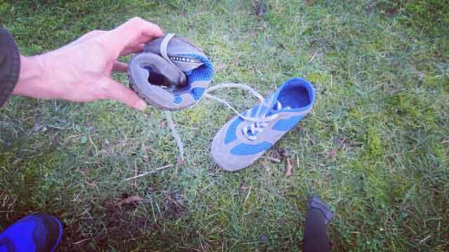 Der Magical Shoes Reflector in blau/grau. Ein Modell liegt auf dem Rasen, ein Modell wird zusammengerollt, um zu zeigen, wie flexibel die Magical Shoes sind.