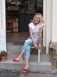 Eine Fraue sitzt am Eingang eines Geschäfts, an den Füßen die Ballerinas von Joe Nimble in rot