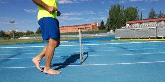 Mit Sport-Barfußschuhe laufen Sie fast so, als seien Sie barfuß unterwegs - so wie dieser Läufer, der barfuß auf einer Tartanbahn trainiert.