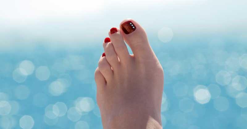 Man sieht einen Fuß, im Hintergrund verschwommen der Ozean. Die Zehen stehen nicht gerade, der große Zeh ist nach innen gebogen.