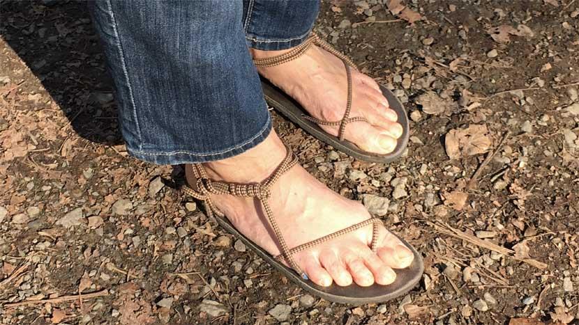 Man sieht zwei Füße auf Waldboden, die mit Tarasoles bekleidet sind. Die Schnürung ist hellbraun gemustert, die Sohle dunkelbraun.