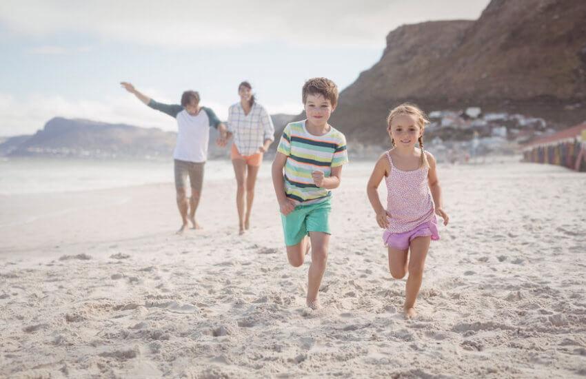 Am Meer: Zwei Kinder rennen lachend und barfuß über den Strand. Im Hintergrund gehen die Eltern spazieren.