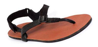 Eine Barfußsandale von Shamma Sandals: Der Riemen ist schwarz, das Fußbett ist aus Ziegenleder und ist hellbraun, die Sohle schwarz.