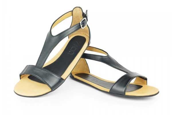 Die Barfuß-Sandal ZAQQ Chiq in schwarz mit einem schwarzen Lederriemen, der sich über Fußrücken, Zehen und Knöchel zieht und mit einer dezenten Metalllasche zugebunden wird.