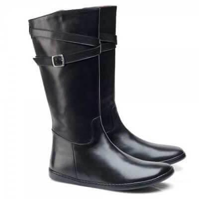 Zu sehen ist das Modell ATTRAQ vonZAQQ. Ein Stiefel, der bis fast unter die Knie reicht. Im oberen Drtittel umspannt ein Lederriemen das Schienbein, befstigt wird dieser mit einer Schnalle.