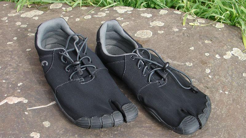 Man sieht den Freet Leap in schwarz auf einem Stein liegen. Die Schnürung ist grau, das Innenfutter auch. Über den Zehen ist eine Zehenkappe, welche die Zehen schützt.