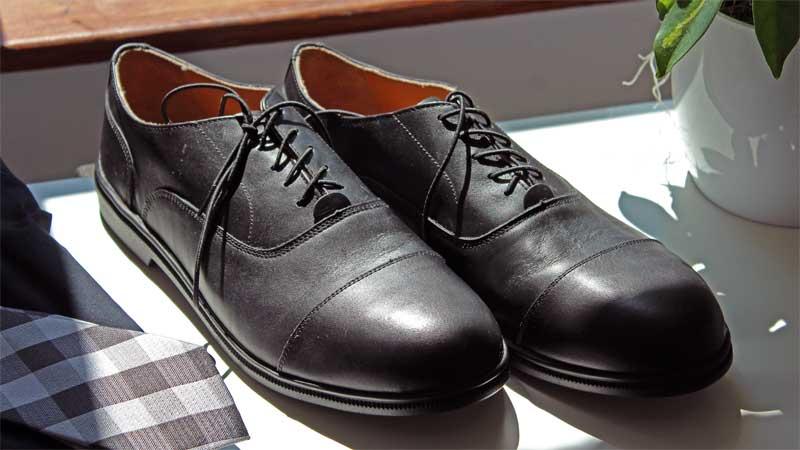 Ein Paar Caretss stehen auf einem weißen Regal. Die Schuhe sind schwarz.
