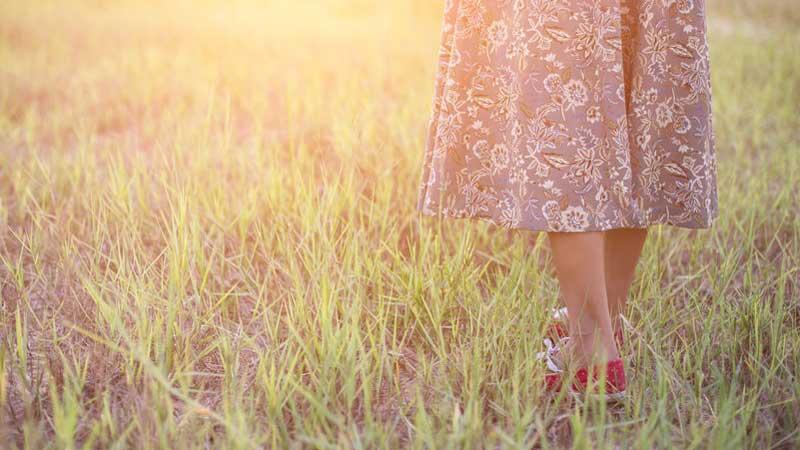 Eine Frau geht in der Abendsonne über eine Wiese. Begleitet ist sie nur mit einem Rock und Damen-Barfußschuhen.