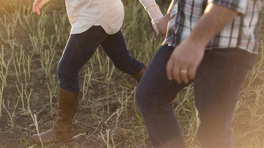 Eine Frau geht in Barfuß-Stiefeln, die bis zu den Knien reichen, über ein Feld spazieren. Sie wird von einem Mann begleitet. Von beiden sieht man nur die Beine und die Hüfte.