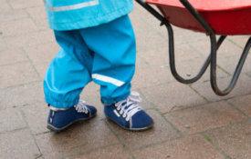 Ein kleiner Junge hat ein Paar Leguanito aktiv am Fuß und schiebt damit eine rote Schubkarre