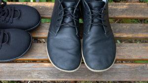 Groundies Barfußschuhe von oben fotografiert, im Hintergrund eine Bank. Links ein Paar aus schwarzem Mesh, rechts die Groundies Milano aus schwarzem Rindleder.