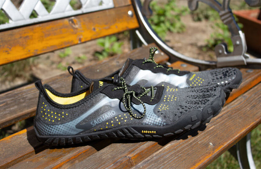 Ein Paar Saguaro Barfußschuhe liegt auf einer Holzbank. Die Schuhe sind schwarz, mit silber-gelben Punkten und Streifen durchzogen.