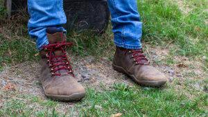 Der Autor Dirk sitzt mit Barfuß-Wanderschuhen von Vivobarefoot auf einer Bank. Die Schuhe sind braun mit roten Schnürsenkeln. Es sind Wanderstiefel.