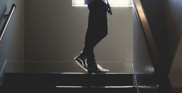 Ein Mann trägt Barfußschuhe und geht in einem dunkeln Treppenhaus die Treppen hoch