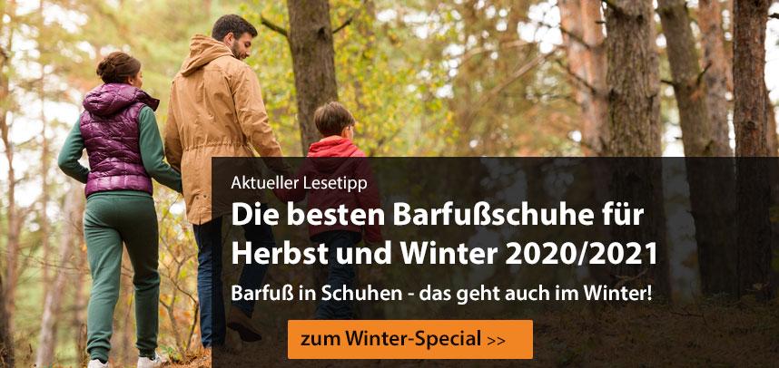 Eine Familie läuft mit Barfußschuhen durch einen Wald spazieren.