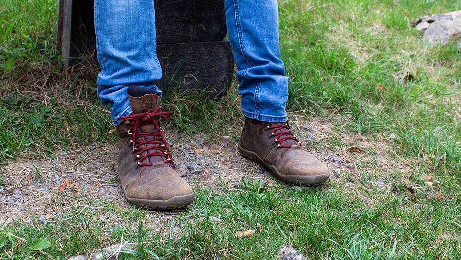 Der Vivobarefoot Tracker Firm Ground im Test - hier sitze ich mit den braunen Schuhen auf einer Bank.