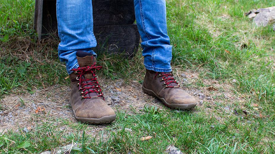 Ich sitze mit Barfuß-Wanderschuhen auf einer Bank. Zu sehen ist ein Modell in brauner Farbe und Stiefelform, mit roten Schnürsenkeln.