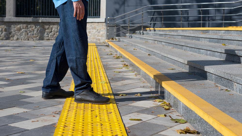 Ein Mann geht auf eine Treppe zu. Er triit mit seinem Fuß auf Markierungssteine, die etwas 30 Zentimeter vor der Treppe sind.