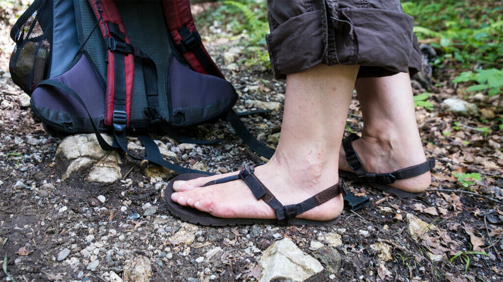 Das Bild zeigt mich, wie ich mit den Barfußsandalen von Pies Sucios vor meinem Rucksack stehe. Die Sandalen haben eine braune Sohle und eine braune Schnürung.